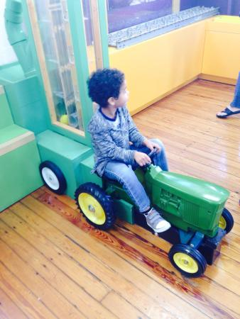 Schoolhouse Children's Museum and Learning Center: Riding the tractor which helped push all the balls through. Then it wasn't working half and hour