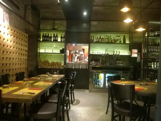La Madama Della Rocca: l'interno del ristorante/pizzeria con vista della cucina