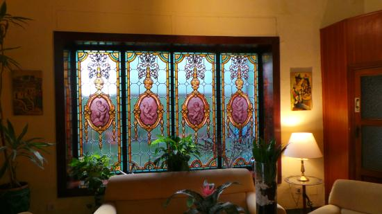 Hotel California : Sofas and beatiful window near reception area, in-keeping with the Spanish theme.
