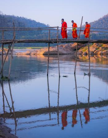 Luang Prabang, Laos: Three monks cross bamboo bridge