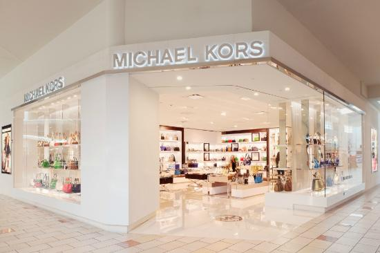 My michael kors bag was from macys, similar price too. Don't know the design or style but it's a fairly large brown one, with gold chains.. Plus, if you take Id, passport or drivers licence to customer services, they give you a 10% discount card.