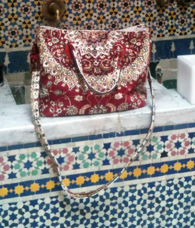 Riad Tizwa Fes: Carpet bag on the water feature in the courtyard