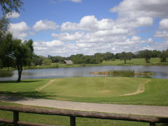 Skukuza Golf Course: Vue sur les greens du 9 trous au-delà du plan d'eau depuis la terrasse du club house