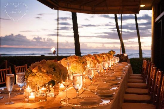a candle lit dinner service as the sun sets over the ocean, here, Beach House/