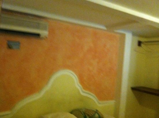 Hotel Villa Florencia Centro: Room showing opening for clothes. Headboard is cement painted