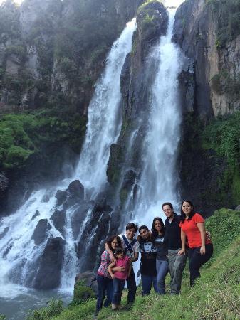 Fotografía de familia poblana con la cascada Quetzalapan de fondo
