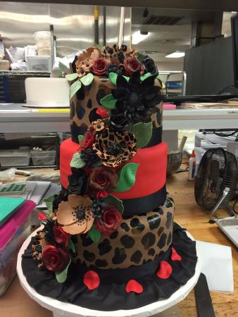 Country Table Restaurant: Hand painted hand made animal print flowers decorate this 3 tier fondant cake