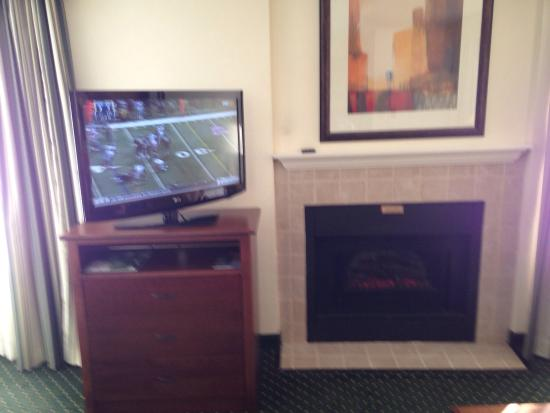 Residence Inn Charlotte University Research Park: The fireplace, electric, and TV in a king-bed room.