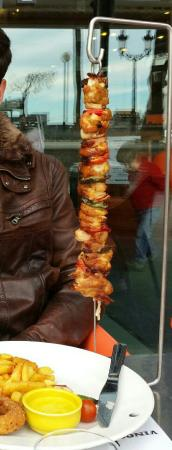 Sports Bar Sitges: Buenísima brocheta de pollo acompañada de patatas fritas, aros de cebolla y salsa curry.