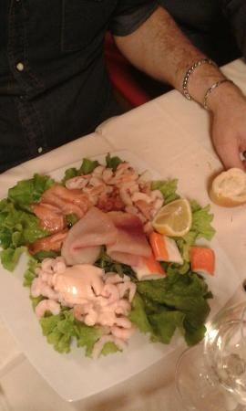 Antipasto misto di mare con gamberetti in salsa rosa su una foglia di insalata, surimi, salmone,