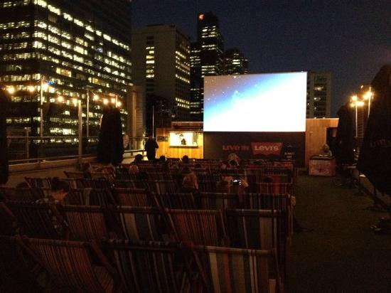 Rooftop Cinema: big screen with city buildings all around