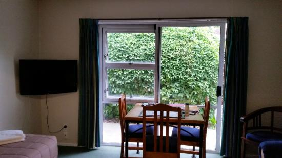 Hagley Park Motel : Living room area with couch, table and single bed