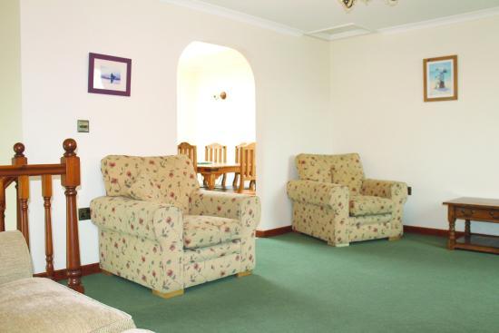 Tregurrian Villas at Watergate Bay: Sitting room showing archway through to kitchen/diner