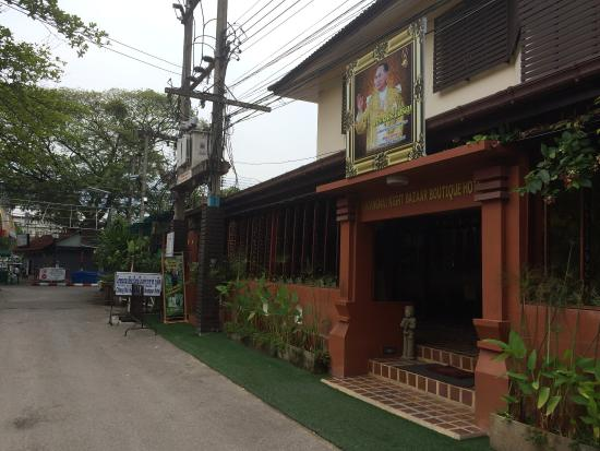 Chiangmai Night Bazaar Boutique Hotel: Entrance to hotel - Anusarn market entry in background near red and white boom gate