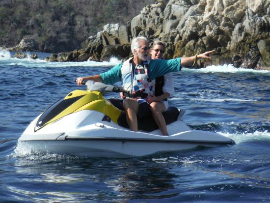 "Huatulco Watersports Jet Ski and Boat Tours: Pointing at the famous ""Face"" in the cliff near a bay in Huatulco."