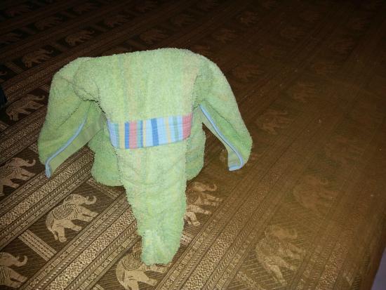 phuketgreenhome: une serviette de bain décore le couvre-lit
