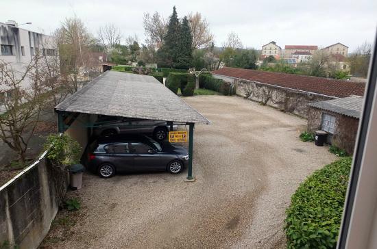 Europ'Hotel: Le parking couvert avec la piscine en fond de terrain