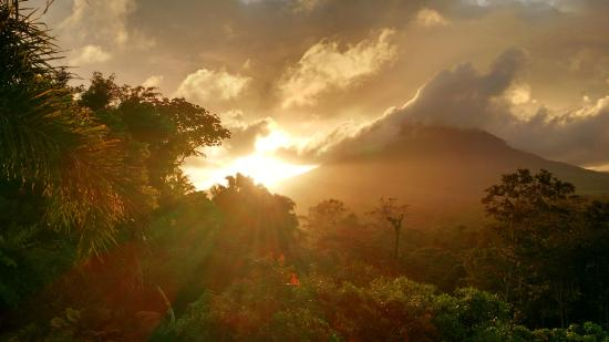 Lost Iguana Resort & Spa: Sunrise over the Arenal volcano as seen from our room balcony