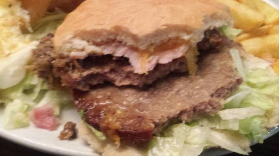 Madisons: Burger showing darkened area of sausage like meat
