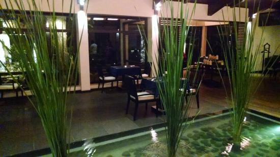 The Raintree: Indoor section with water/pond in middle of restaurant - tables against window