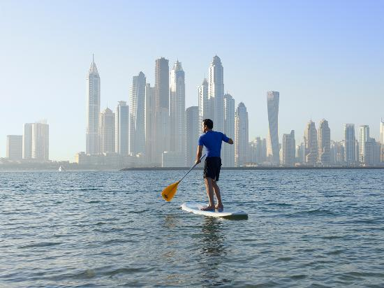 Paddle boarding from Fairmont the Palm with the city of Dubai in the background