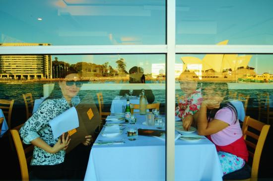 Peter Doyle @ The Quay: husband taking a picture from outside the window to capture the Opera House reflection.