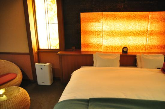 Hotel Tamanoyu: Room featuring a warm wooden decor, a double bed and soft indirect lighting