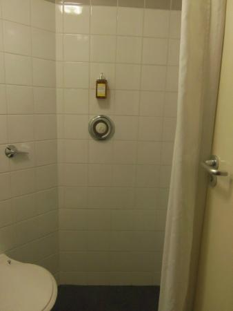KM Central : The shower that is just built into the wall with a drain in the floor.
