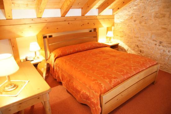 Camera doppia con muro in pietra a vista e soffitto in travi di ...