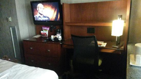 Kellogg Hotel And Conference Center: Desk and entertainment area with flat screen tv, single cup coffee maker, and six available elec