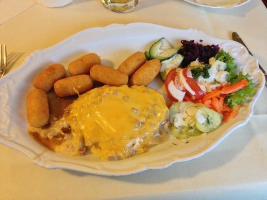 Niedernissa, Alemania: Schweinesteak mit Würzfleisch und Käseüberbacken, dazu Kroketten und Salat