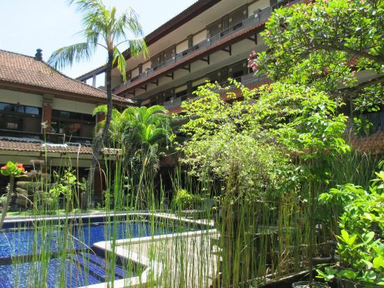 Hotel Puri Tanah Lot: coin de piscine avec ma chambre située derrière les arbres au premier
