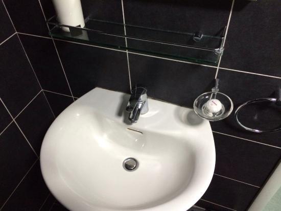 Eher dreckiges Badezimmer mit Waschmaschine. Viele Wasserflecken ...