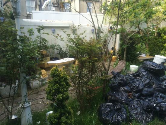Mansion Lions Hotel: BIN BAGS IN GARDEN WITH PAINT POTS