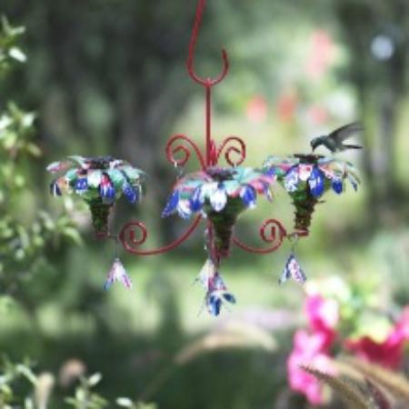 Flowers made out of aluminum juice cans adorn this chandelier camino silvestre flowers made out of aluminum juice cans adorn this chandelier hummingbird feeder mozeypictures Gallery