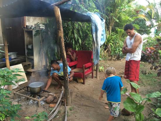 Namatakula, Fiji: Sitai & Mariani cooking breadfruit on a fire out the back