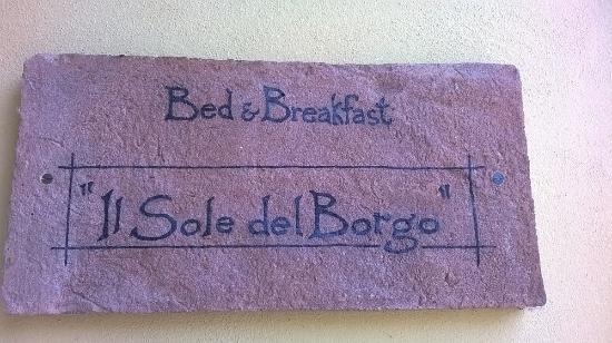 Il Sole Del Borgo : La piccola insegna all'entrata, dalla strada principale