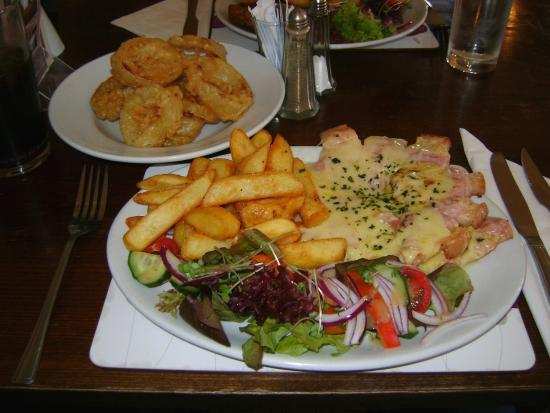 Queen Victoria Inn: My partners meal 1 (Gammon steak topped with cheese, with chips, salad and onion rings £12.75)