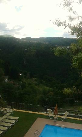 Tiglio Basso, إيطاليا: vue de la piscine avec village et montagne à l' horizon