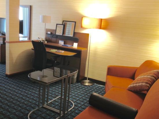 Fairfield Inn & Suites Dulles Airport : Sitting area with desk, sofa bed, TV and table