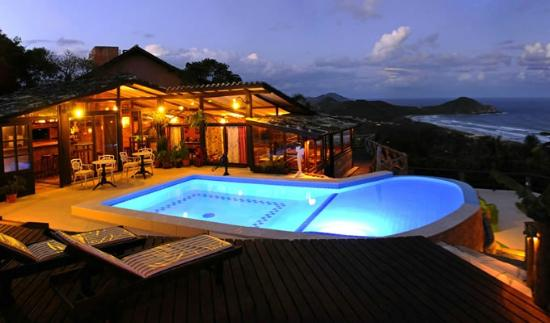 Pousada Caminho do Rei: Pool deck and restaurant at night