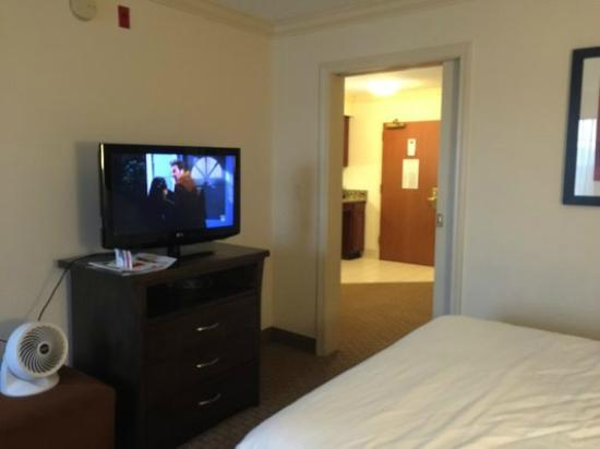 Holiday Inn Express Amherst-Hadley: TV in bedroom looking towards living/kitchen area