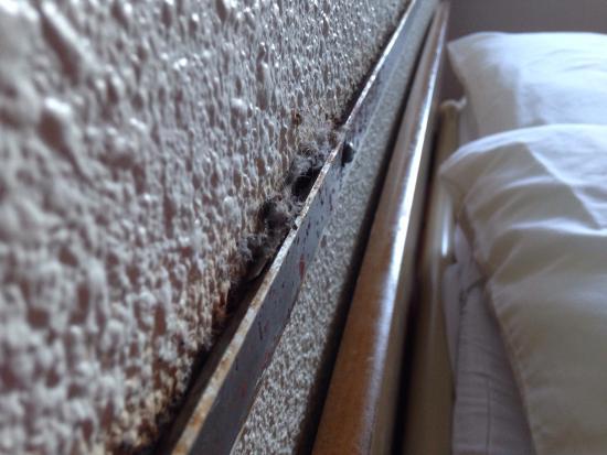 Premiere Classe Le Blanc Mesnil : Tête de lit avec barre en métal au dessus remplit de poussière