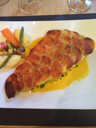 Blonay, Switzerland: Filet de loup de mer en écaille de pommes de terre sur lit de poireau à la crème safranée