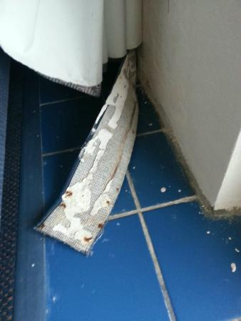 Acropolis Oceanfront Resort: Found baseboard like this when we walked in.  Bugs crawling on inside of baseboards.