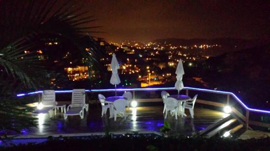 Pousada Santorini: Vista noturna da picina com com a cidade ao fundo