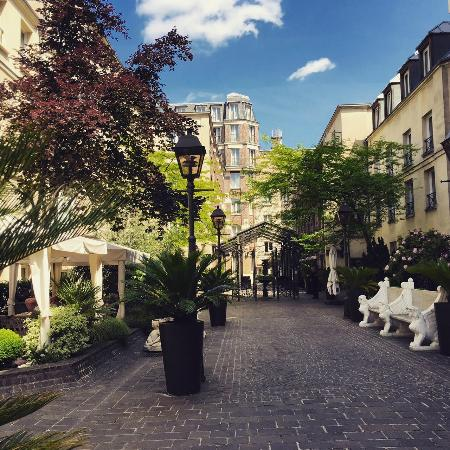 Courtyard surrounded by several buildings with rooms for Hotel les jardins paris