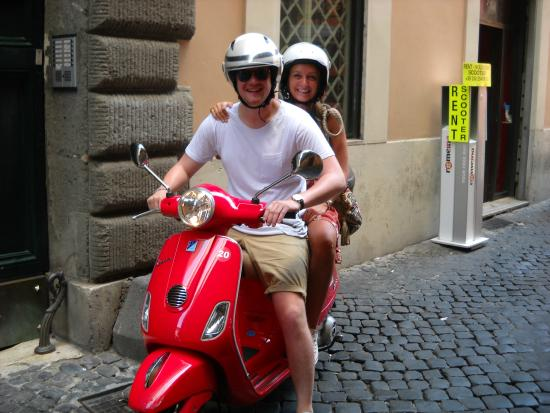 another couple from holland smiling on board a red vespa picture
