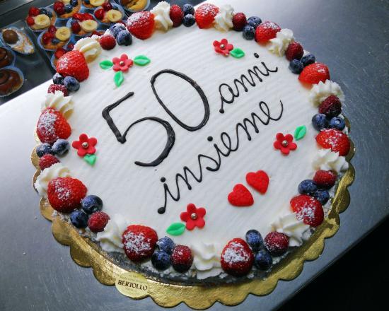 Idee Fotografiche Anniversario : Torta di anniversario ricoperta di panna con frutta fresca e