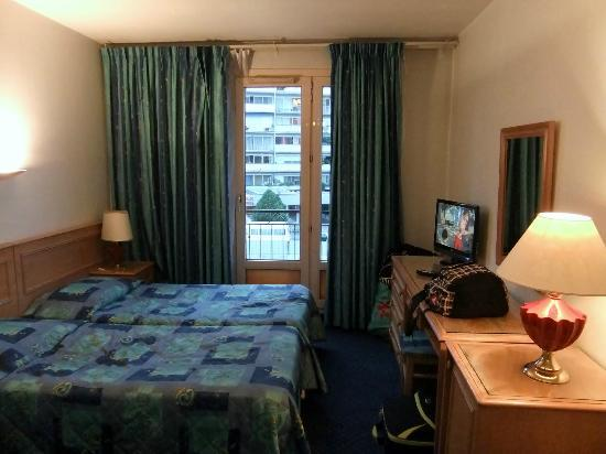 France Hotel: What the bedrooms look like. A medium sized bathroom. A medium sized fridge and a TV. The beds a